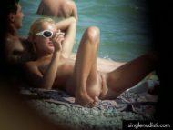 Nudista a gambe aperte fuma sigaretta